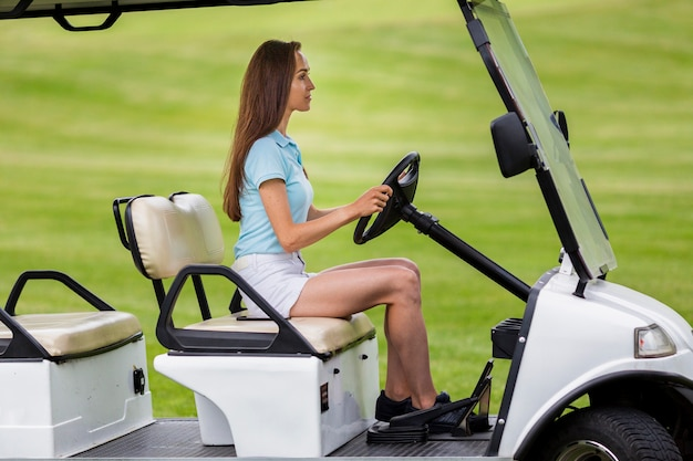 Nettes junges mädchen, das golfmobil fährt