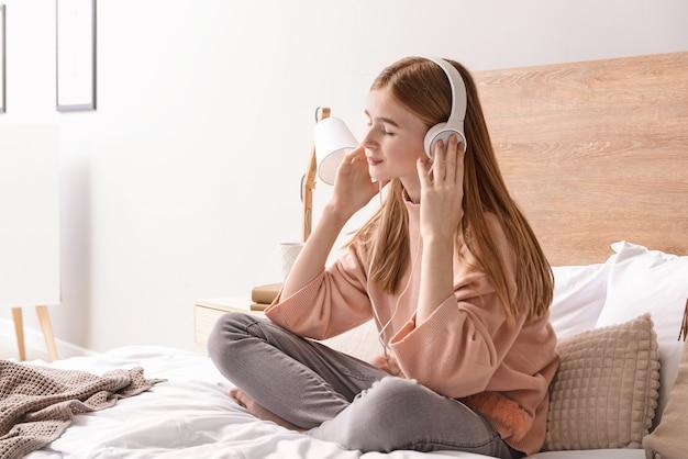 Nettes junges mädchen, das musik im schlafzimmer zu hause hört