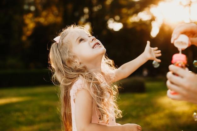 Nettes junges mädchen, das seifenballons gegen sonnenuntergang fängt. schönes kleines kind, das draußen spielt.