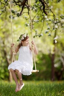 Nettes junges mädchen, das spaß auf einer schaukel im blühenden alten apfelbaumgarten hat. sonniger tag. frühlingsaktivitäten im freien für kinder