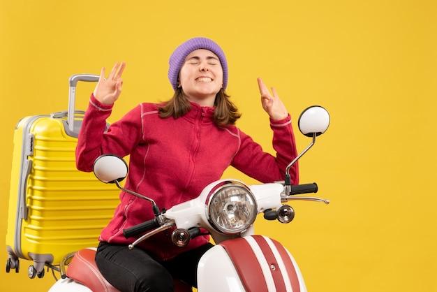 Nettes junges mädchen der vorderansicht auf moped, das okey zeichen macht