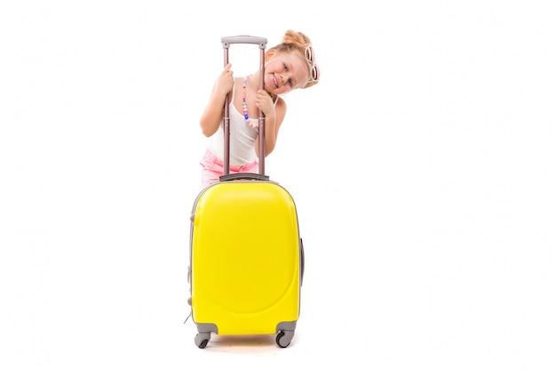 Nettes junges mädchen im weißen hemd, in den rosa kurzen hosen und in der sonnenbrille stehen nahe gelbem koffer