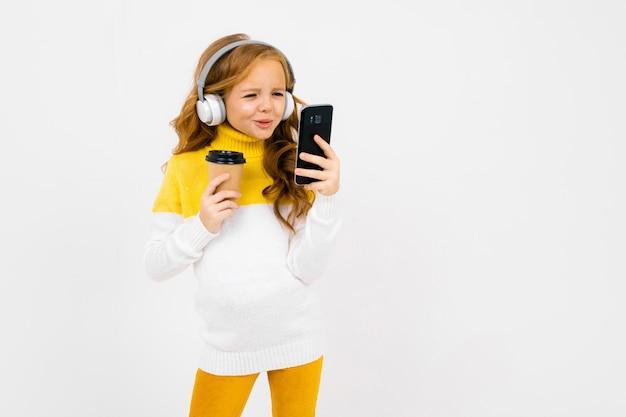 Nettes junges mädchen in den weißen kopfhörern betrachtet das telefon und hält ein glas
