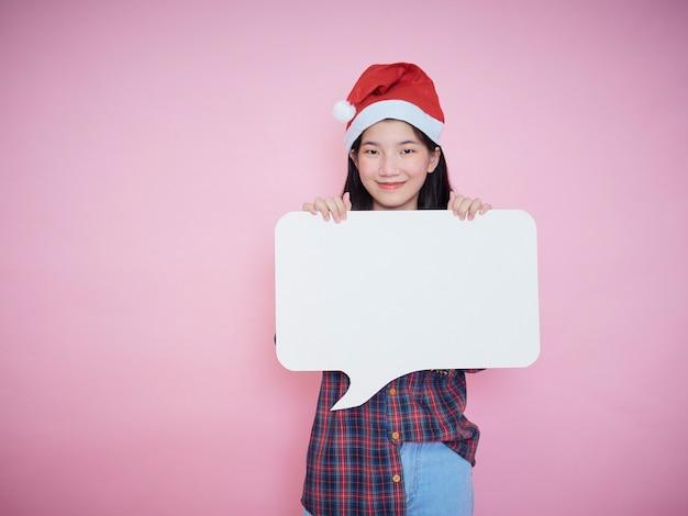 Nettes junges mädchen in der weihnachtsmütze, die weißes leeres plakat auf rosa hintergrund hält