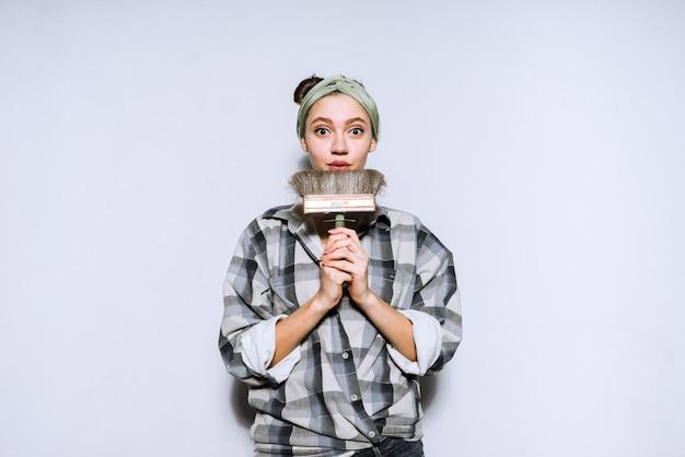 Nettes junges mädchen in einem karierten hemd, das einen pinsel zum streichen der wände hält und reparaturen in ihrer neuen wohnung durchführt