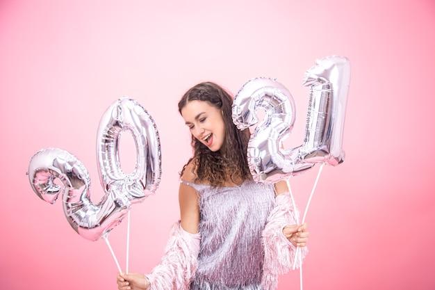 Nettes junges mädchen in festlichen kleidern freut sich das neue jahr auf einer rosa wand mit luftballons für das neujahrskonzept
