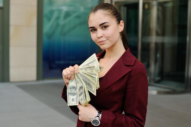 Nettes junges mädchen mit einem bündel von dollars in den händen