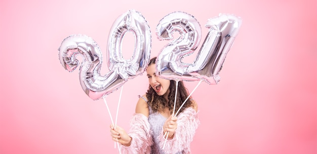 Nettes junges mädchen mit einem lächeln in einem festlichen outfit, das gegen einen rosa studiohintergrund aufwirft und silberne luftballons für das neujahrskonzept hält