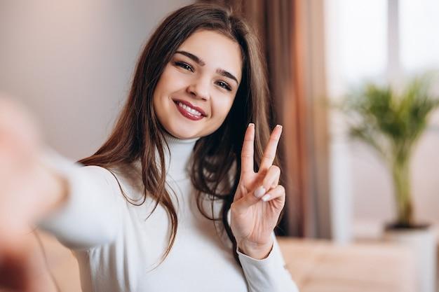 Nettes junges mädchen mit hübschem lächeln nimmt selfie von ihr zu hause