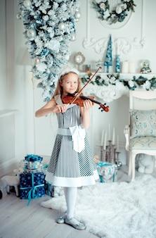 Nettes junges mädchen mit violine im weihnachtsdekorationsraum.