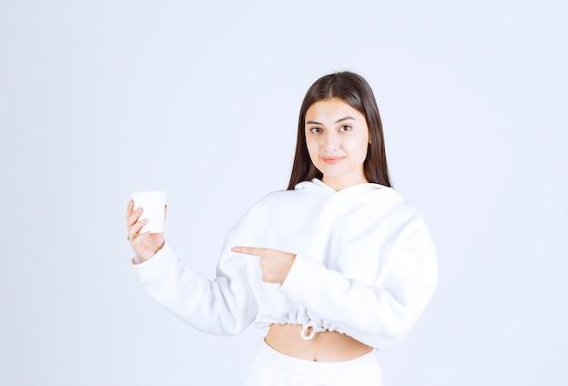 Nettes junges mädchenmodell, das auf einen plastikbecher zeigt.