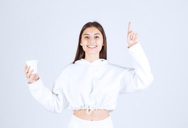Nettes junges mädchenmodell mit einem plastikbecher, der nach oben zeigt.