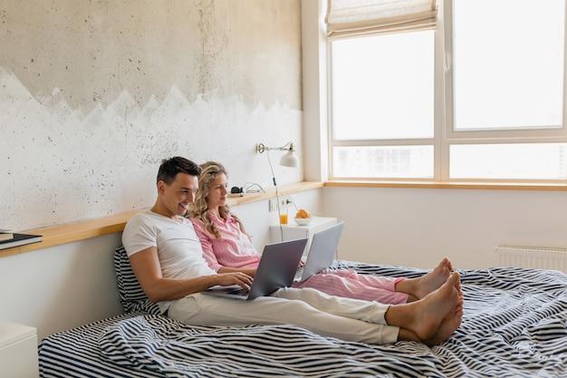 Nettes junges paar, das am morgen auf bett sitzt, mann und frau, die am laptop arbeiten