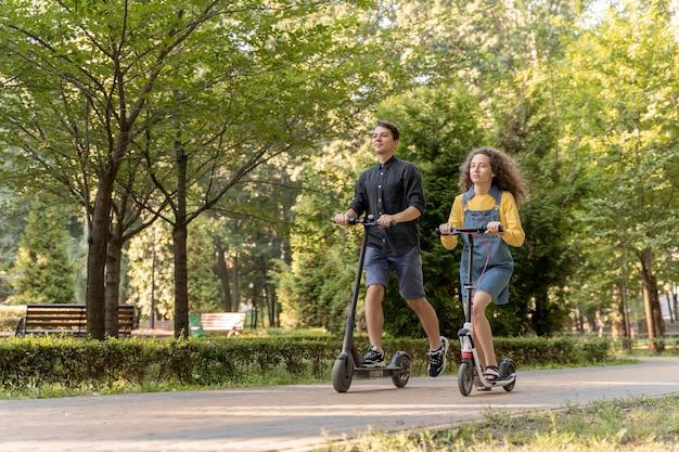 Nettes junges paar, das roller draußen reitet
