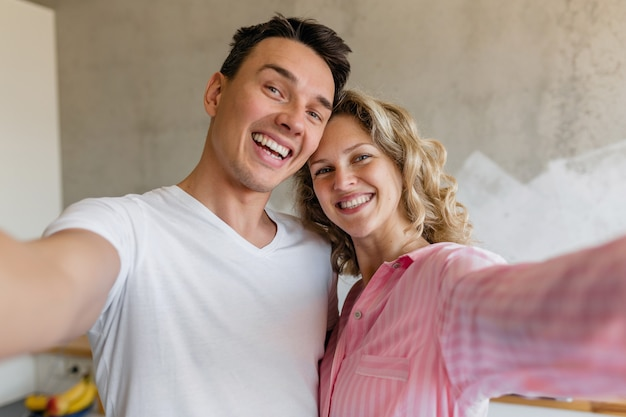Nettes junges paar, das spaß am schlafzimmer am morgen hat, mann und frau, die selfie-foto machen, das pyjamas trägt