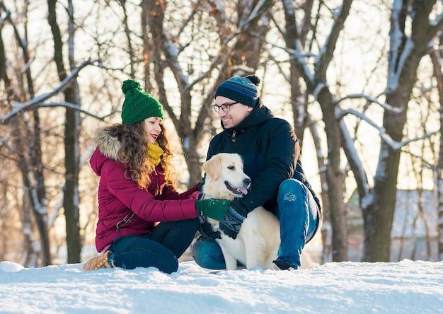 Nettes junges paar, das spaß im winterpark mit ihrem hund golden retriever an einem sonnigen tag und lächeln hat. frau und mann umarmen mit hund in der schneebedeckten winterlandschaft