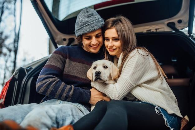 Nettes junges paar hat ein wochenende mit ihrem labrador-retriver, der in ihrem auto sitzt.