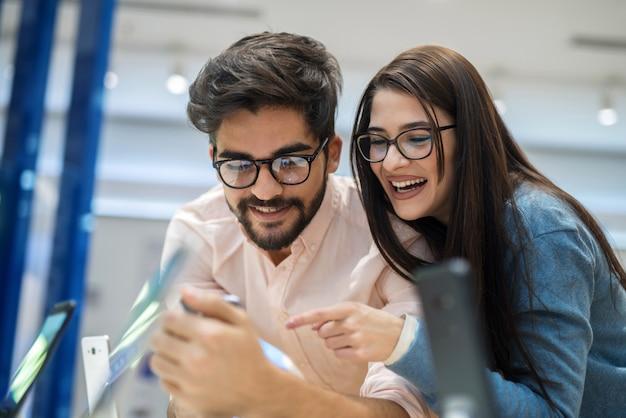 Nettes junges paar im elektronischen geschäft, das einige neue telefone testet. auf der suche nach der idealen ausrüstung.