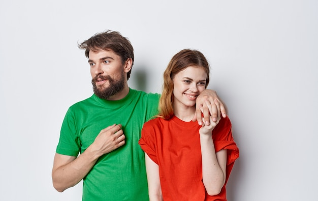 Nettes junges paar in mehrfarbigen t-shirts umarmt lebensstilspaß isoliert.