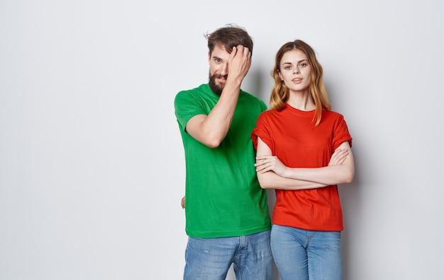 Nettes junges paar in mehrfarbigen t-shirts umarmt lifestyle-spaß isolierten raum