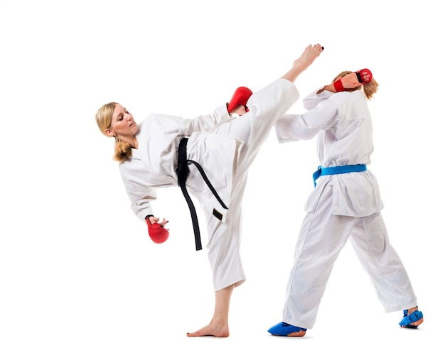 Nettes karate der blonden mädchen trainiert in einem kimono an einer weißen wand