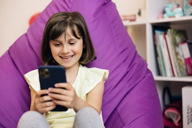 Nettes kaukasisches mädchen, das smartphone hält, das die verwendung von mobilen apps genießt