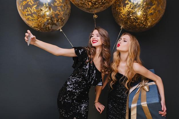 Nettes kaukasisches mädchen mit dem langen lockigen haar, das mit küssendem gesichtsausdruck aufwirft, großes geschenk hält. entspannte junge frau, die selfie mit freund während der weihnachtsfeier macht.