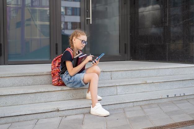 Nettes kaukasisches rothaarigemädchen in brillen mit büchern und rucksack. setzen sie sich und tippen sie auf dem telefon. zur schule gehen. tag des wissens. zurück zum schulkonzept.