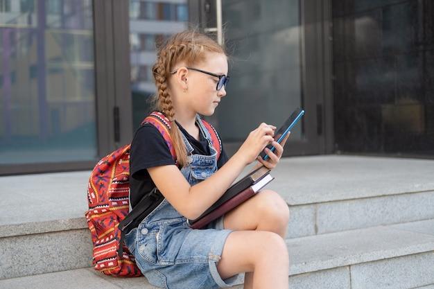 Nettes kaukasisches rothaarigemädchen in brillen mit büchern und rucksack. setzen sie sich und tippen sie auf dem telefon.