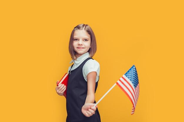 Nettes kaukasisches schulmädchen, das amerikanische flagge zeigt und buch auf gelber hintergrundflagge usa hält