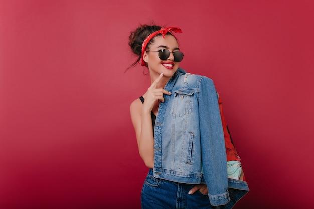 Nettes kaukasisches weibliches modell mit rotem band im braunen haar, das auf rotweinraum aufwirft