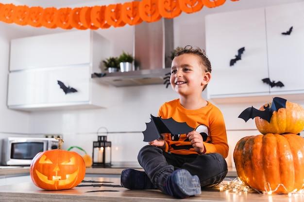 Nettes kind, das am küchentisch sitzt, gekleidet als kürbis, der mit fledermäusen spielt und halloween...
