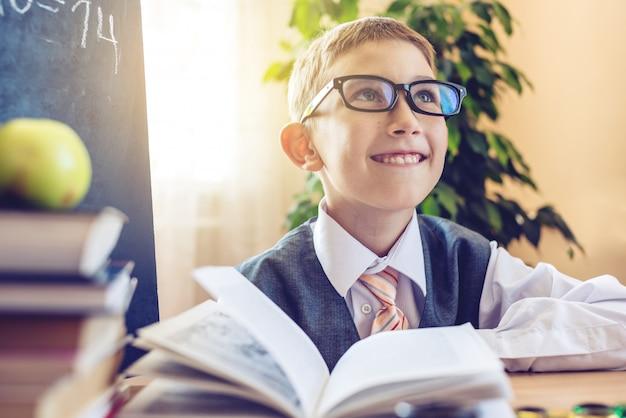 Nettes kind, das am schreibtisch im klassenzimmer sitzt. junge sitzt sorgfältig auf der lektion