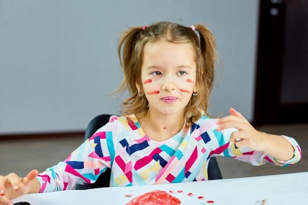 Nettes kind, das am tisch sitzt und mit der hand streifentarnung auf ihr gesicht zeichnet