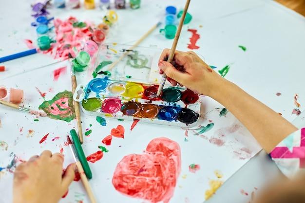Nettes kind, das am tisch sitzt und rotes herz auf weißem papier zeichnet, konzept der kunstschule, mädchenkindmalerei mit aquarellfarben zu hause