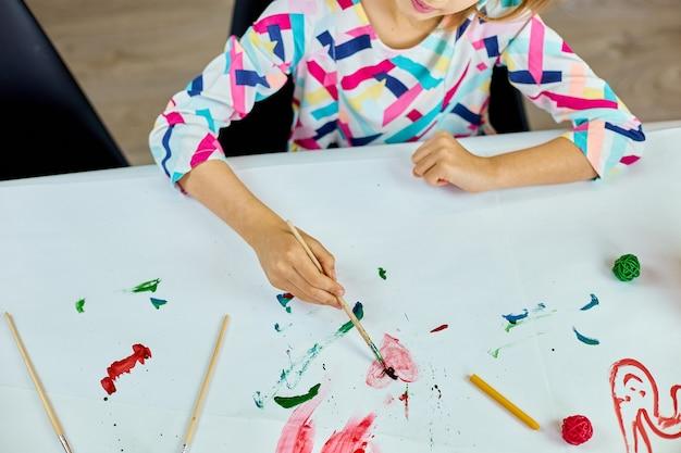 Nettes kind, das am tisch sitzt und rotes herz auf weißem papier zeichnet