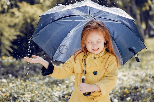 Nettes kind, das an einem regnerischen tag plaiyng ist