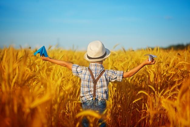Nettes kind, das auf dem goldenen gebiet des weizens an einem sonnigen sommertag geht. junge startet papierflieger. natur im land. rückansicht