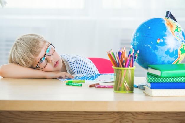 Nettes kind, das auf der lektion langweilt. das kind möchte keine hausaufgaben oder klassenarbeiten machen. unglücklicher schüler.