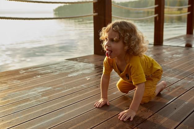 Nettes kind, das bei sonnenuntergang auf pier krabbelt
