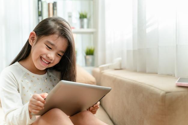 Nettes kind, das eine tablette verwendet und beim auf sofa zu hause sitzen lächelt
