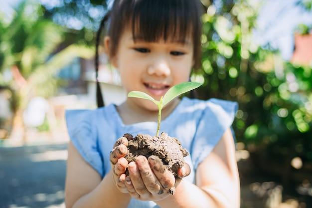 Nettes kind, das einen baum für hilfe pflanzt, um globale erwärmung oder klimawandel zu verhindern und die erde zu retten