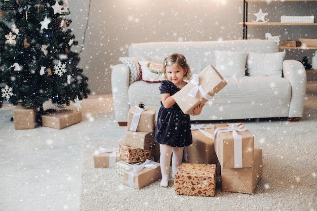 Nettes kind, das geschenkbox in den händen steht, lächelt und hält. entzückendes kind, das im schwarzen kleid trägt. wohnzimmer verziert mit weihnachtsbaum, verzierungen und handwerksgeschenkkästen.