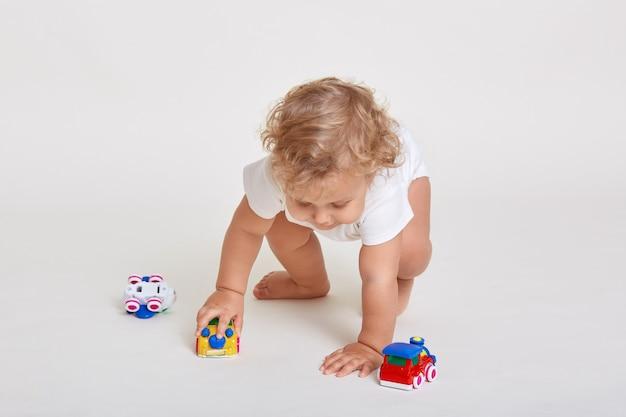 Nettes kind, das mit mehrfarbigem spielzeug spielt, das über weißem raum isoliert wird, körperanzug trägt und barfuß mit spielzeugautos spielt