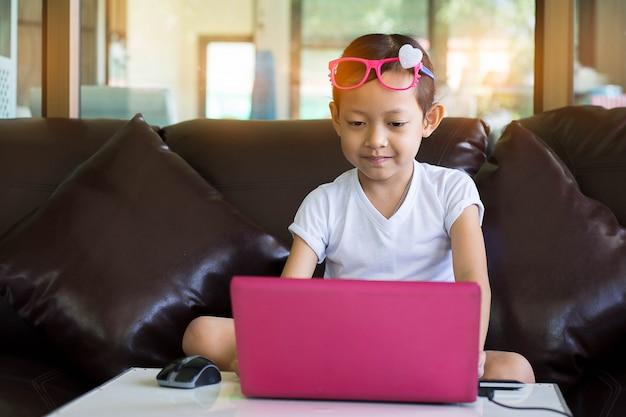 Nettes kind, das zu hause computer spielt. selektiver fokus.