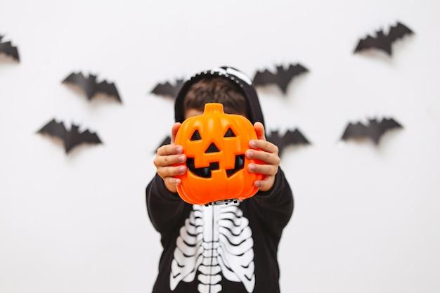 Nettes kind im halloween-kostüm, das mit kürbis aufwirft.