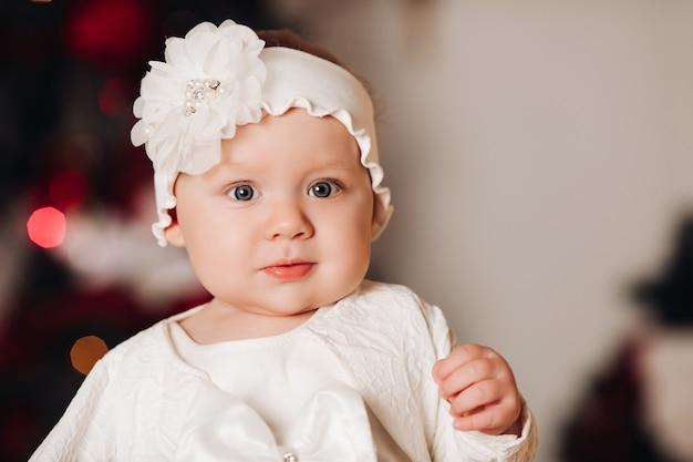 Nettes kind im weißen kleid, das unter weihnachtsbaum aufwirft.