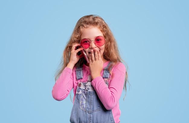 Nettes kind in der trendigen sonnenbrille, die auf handy spricht und mund bedeckt, während sie klatscht und schaut