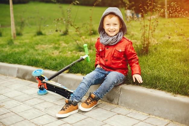 Nettes kind in einem park, der auf einem gras spielt