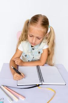 Nettes kind macht hausaufgaben auf weißem hintergrund.
